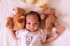 Asian cute baby newborn smile and happy, good mood, on the bed with Teddy bear stock photography