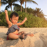 Asian cute baby playing sand. Asian cute baby playing sand on the beach at sunset time Stock Photography