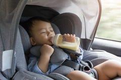Asian cute baby sleepy drinking milk bottle in modern car seat. Stock Photos