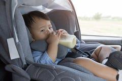 Asian cute baby sleepy drinking milk bottle in modern car seat. Royalty Free Stock Image