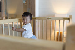 Asian cute baby standing on baby cot. Royalty Free Stock Images