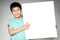 Asian cute boy with big white  blank plate  for add your text . Royalty Free Stock Photos
