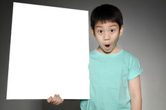 Asian cute boy with big white  blank plate  for add your text . Stock Photo