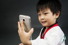 Asian cute boy in karategi costume take a photo by cellphone Stock Photo