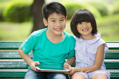 Asian cute boy and little girl are smile and looking the camera. Sitting on a wooden bench in the park,Bangkok Thailand Royalty Free Stock Images