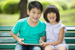 Asian cute boy and little girl are smile and looking the camera. Sitting on a wooden bench in the park,Bangkok Thailand Stock Photos