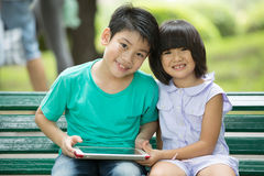 Asian cute boy and little girl are smile and looking the camera. Sitting on a wooden bench in the park,Bangkok Thailand Royalty Free Stock Image