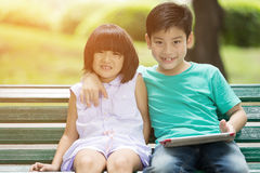 Asian cute boy and little girl are smile and looking the camera. Sitting on a wooden bench in the park,Bangkok Thailand Stock Photography