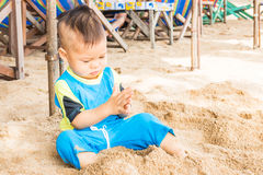 Asian cute boy playing sand on the beach Stock Photo