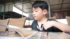 Asian cute boy reading menu book and point . stock video footage
