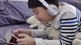 Asian cute boy watching on tablet computer and wearing white headphone with smile face. stock video footage