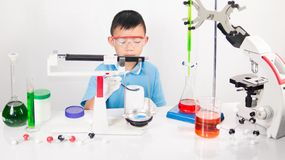 Asian cute child learning science in laboratory on gray whit background. Cute child boy playing and funny in knowledge about lab experiment and instrument of Stock Photo