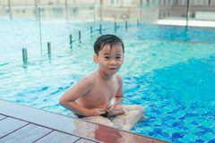 Asian cute child swimming in swimming pool. He playing is funny. On summer holiday on blurred background. Cute boy smile and swim on daytime and light of sun stock photography