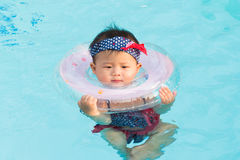 Asian cute eight month baby relax swimming pool. Asian cute eight month baby relax swimming pool, Active healthy first time playing swim in pool at home Stock Photo