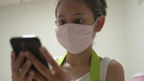 Asian cute girl in apron wearing protective mask using mobile phone for social online communication with her friend.