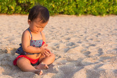 Asian cute girl baby playing sand on the beach. Asian cute girl baby playing sand on the beach, sunset time background. Nine mouth baby is excited first time to Stock Photos