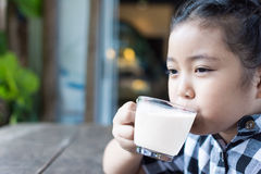 Asian cute girl drinking milk and use smartphone in coffee shop. Stock Images