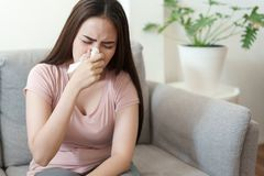 Asian Cute of  girl having  flu season and sneeze using paper tissues sitting on sofa at home, Health and illness concepts
