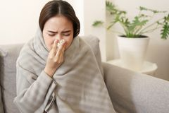 Asian Cute of  girl having  flu season  and  sneeze  using paper tissues sitting on sofa at home, Putting blanket, Health and
