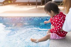Asian cute girl kid enjoying kick water in the pool. Asian cute girl kid enjoying kick water in the pool, sunny light background, vacation holidays happiness royalty free stock photo