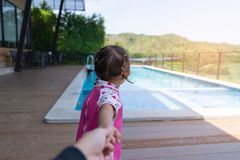 Asian cute girl kid pull hand father walk to the pool. Asian cute girl kid pull hand father walk to the pool, sunny light background, vacation holidays Stock Photos