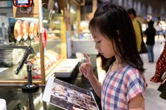 Asian cute girl ordering from menu. At food court in mall royalty free stock photos