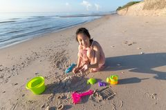 Asian cute girl playing sand on the beach, summer vacation and r stock photography