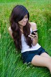 Asian cute girl texting on meadow. With happy face Royalty Free Stock Photo