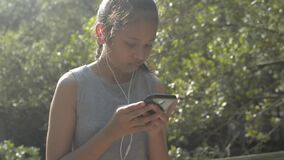 Asian cute girl using mobile phone with earphones and standing among mangrove forest under sunlight in the morning.