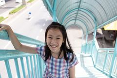 Asian cute girl walk across the pedestrian overpass,for safety c royalty free stock photo