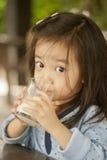 Asian cute little girl drinking milk. Closeup portrait of asian cute little girl drinking milk Royalty Free Stock Photography