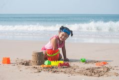 Asian cute little girl made a Sand castle on the beach with her