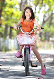 Asian cute little girl riding bicycle outdoor Royalty Free Stock Photos