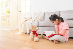 Asian cute little girl sitting on the wooden floor. Studying the comic book feel very boring at home in the living room with her favorite teddy bear waiting for Stock Images