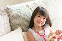 Asian cute little girl is smiling and playing doctor with stethoscope. Kid and health care concept. royalty free stock photography