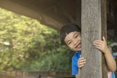 Asian cute little girl sneaks behide pole. Asian cute little girl feel fun playing hide and seek by sneak behind wooden pole. Little girl with smiling face Stock Photos