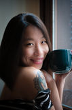 Asian cute woman smiles with green mug Stock Image