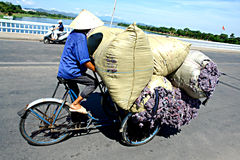 Asian cyclist on his bike. A salesman riding his bike with his selling material on it Stock Photography