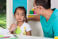 Asian dad with sick daughter. At doctor's office royalty free stock photography