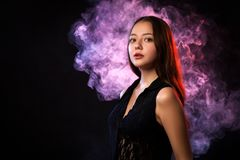 Asian dark-haired woman. In a black dress posing against a background of red and red smoke from a vape on a black background stock photo
