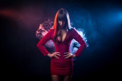 Asian dark-haired woman. Young dark-haired woman in a red dress posing against a background of red and blue smoke from a vape on a black background royalty free stock photo