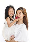 Asian daughter and mom eating red apple. Royalty Free Stock Images