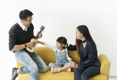 Asian daughter playing guitar and singing with father and mother royalty free stock images