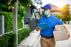 Free Asian Delivery Man In Blue T-shirt Carrying Parcel Box Stock Photos - 179691043