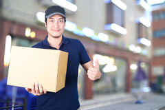 Asian Delivery man thumbs up with cardboard box on blurred backg. Asian smile Delivery man thumbs up with cardboard box in hand standing on blurred shop Royalty Free Stock Photography