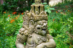 Asian Demon. Statue with flowers in the background stock photo