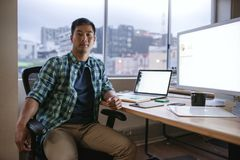 Asian designer working late at his desk in an office. Portrait of a focused young Asian designer sitting at his desk while working late in a modern office Royalty Free Stock Images