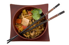 Asian Dinner. Stir Fry in a wooden bowl with chop sticks isolated over white Royalty Free Stock Photo