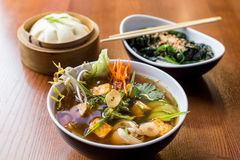 Asian dinner dishes - bao, soup and salad Stock Image