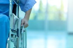 Asian disabled man is sitting in a wheelchair. He holds his hand stock photos